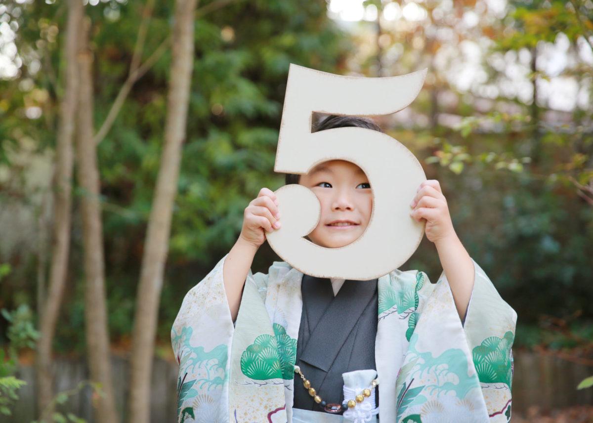 七五三の5歳のお祝いの子が5の数字をもって撮影している